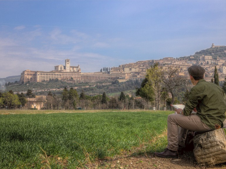the city of Assisi on the top of an hill seen by a painter sitting at the foot of the hill