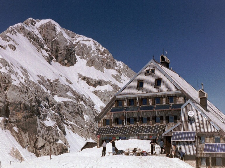 A mountan hut surrounded by snow at the foot of a mountain