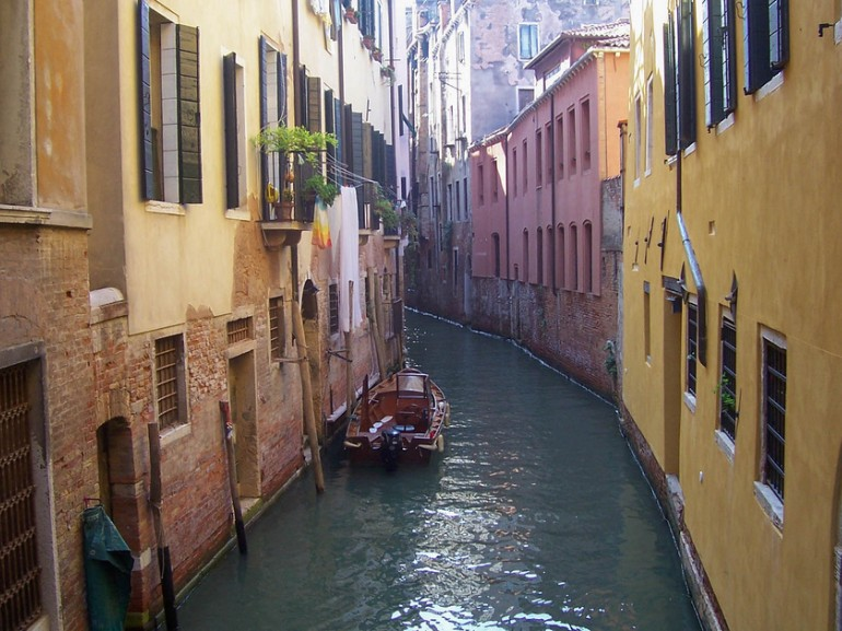 a small water channel in Venice, with houses and boats