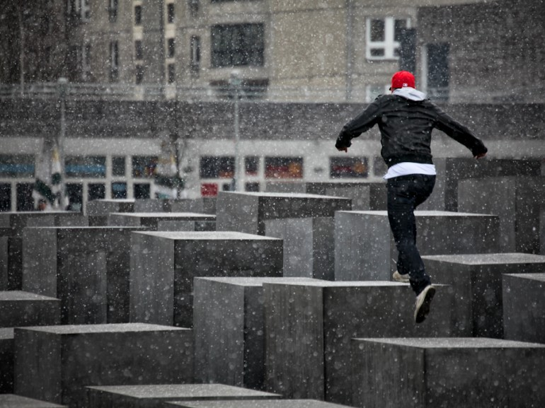 a guy walking on squared rocks while it is snowing