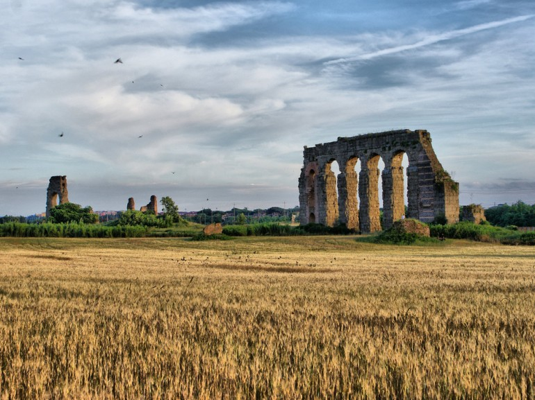 in a field, the rest of a roman aqueduct made of stones