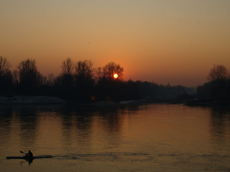 Sunset at Po River. A canoeist breaks into this quiet scenary
