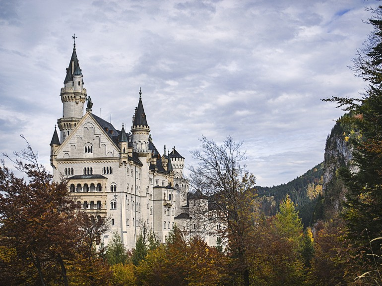 the beautiful castle with its towers on the hill surrounded by autumn trees