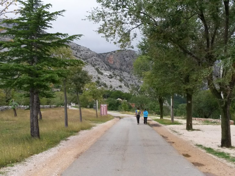 two people walking on the path towards the park. On the background you can se mountains