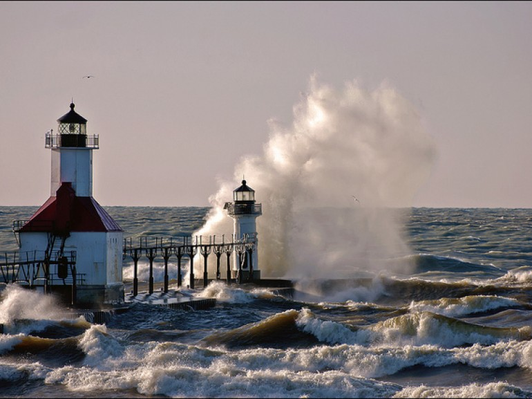 a lighthouse on the shore with waves