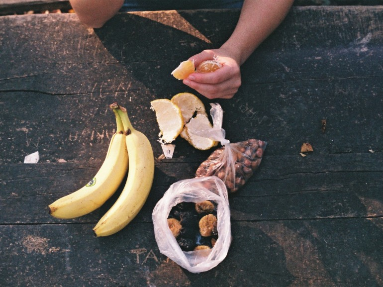 on a table made of wooden a banana and other fruits. a guy is eating