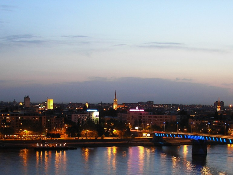 the city at night with its lights: a bridge on the river and buildings