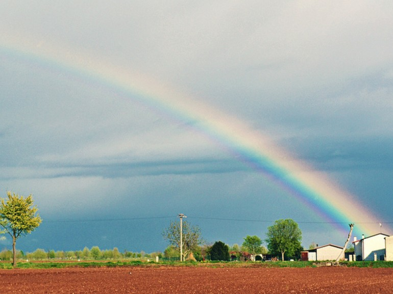 flat land, a country house and the rainbow in the sky