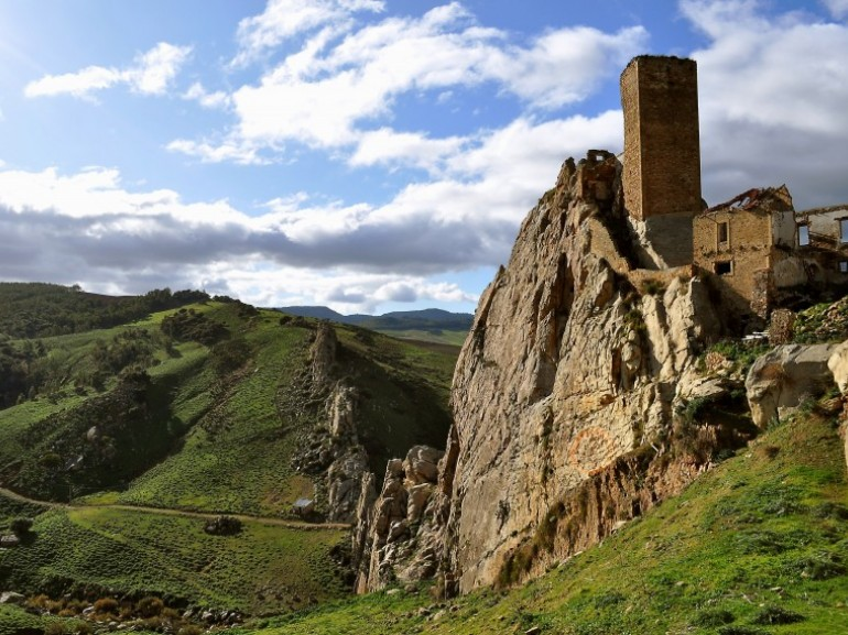 an ancient castle built on the rock on the top of an hill. A tower is still well visible