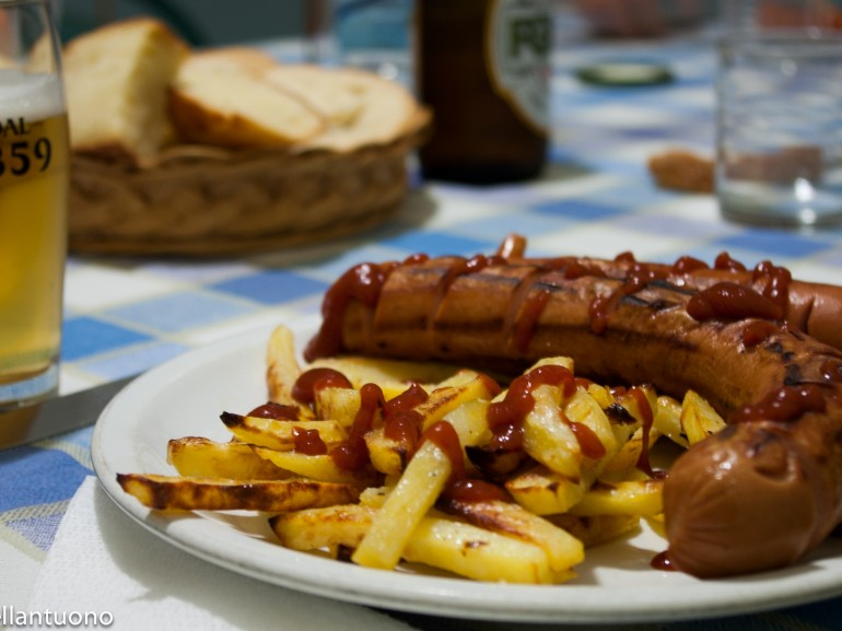 a plate with sausages and french fries on the table with a glass of beer
