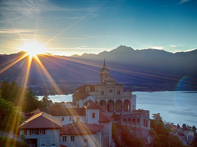 locarno lake seen from the top of an hill where a church stands in the morning light