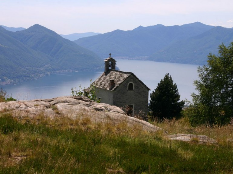 a small house on an hill. On the back you can see the lake surrounded by green mountains