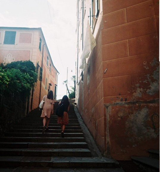 Two girls are going up the stairs in the historical centre of Camogli
