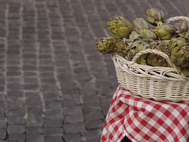 a basket full of artichockes on a table on the street
