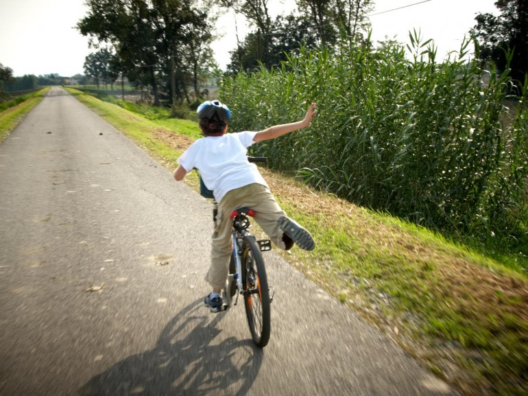 A child on a bicycle along a path near the river