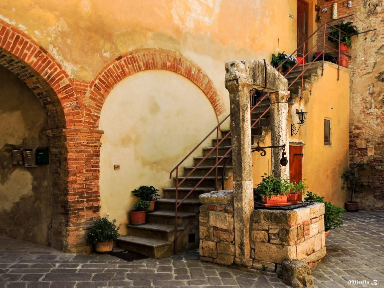 A glimpse of San Quirico d'Orcia with one of the characteristic stone fountain