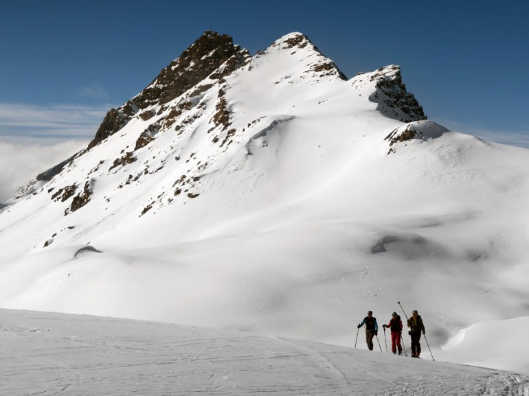 three people walking on the snow at the foot of a rocky mountain