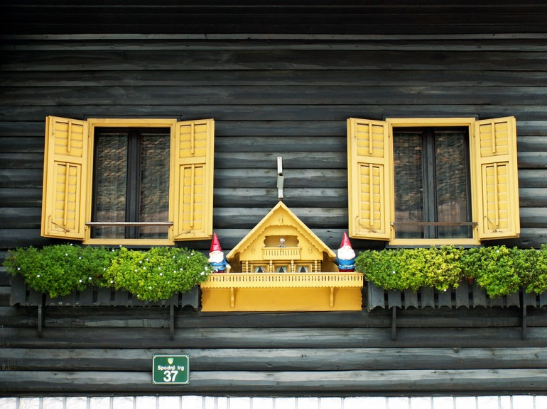 the wooden wall of an house with yellow balconies