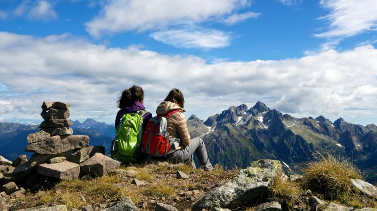 Two girl on the top of the mountains watching at the horizon, where you can see Cima d'Asta