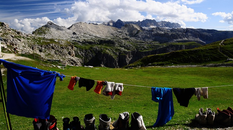 some clothes and shoes drying in the sun, mountains in the background